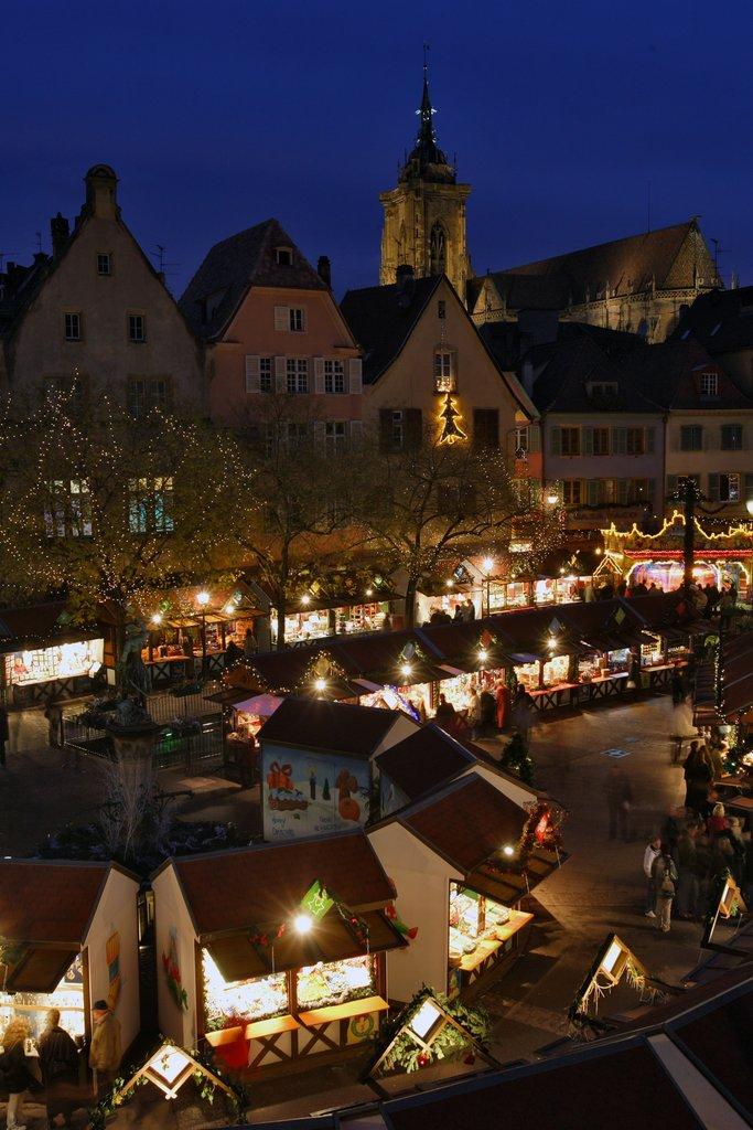 Vue nocturne du clocher de la collégiale Saint-Martin et d'un marché de Noël, place de l'Ancienne Douane