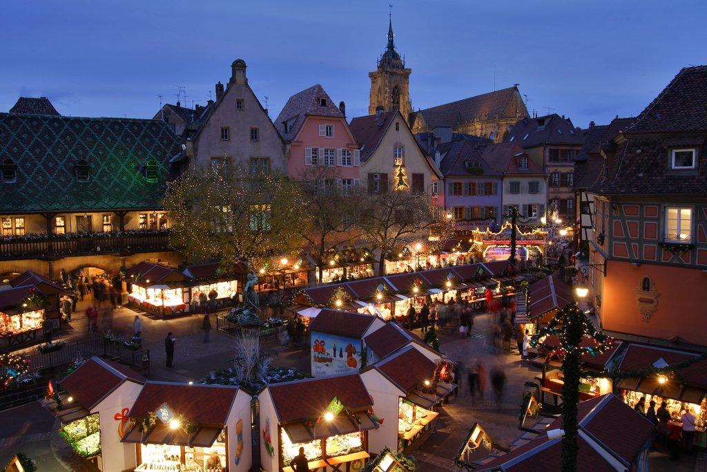 Marché de Noël illuminé avec le Koïfhus et la collégiale Saint-Martin, place de l'Ancienne Douane